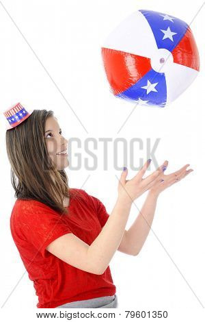 An attractive young teen wearing a tiny Uncle Sam hat.  She's playing catch with an inflated star-studded red, white and blue ball.  On a white background.
