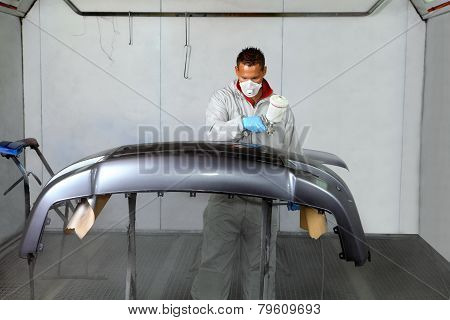 Painters Use Spray Guns To Apply Paint To A Bumper.