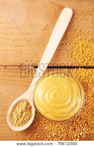 Composition of different kinds of mustard on wooden background poster