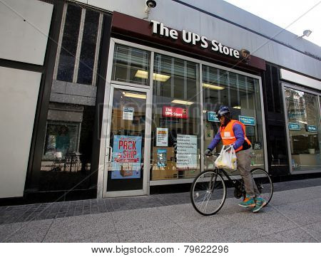 NEW YORK CITY - MONDAY, DEC. 29, 2014: A bicycle messenger rides by a UPS Store. The UPS Store network is the world's largest franchisor of retail shipping, postal,  and business service centers