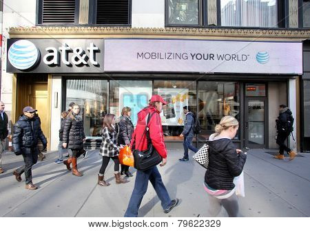 NEW YORK CITY - MONDAY, DEC. 29, 2014: Pedestrians walk past an AT&T mobile telephone store. AT&T Mobility, formerly known as Cingular Wireless, is a wholly owned subsidiary of AT&T