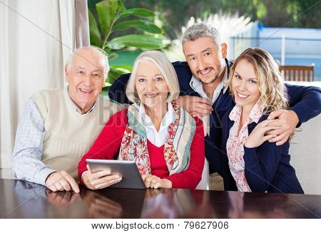 Portrait of happy senior couple and grandchildren with digital tablet in nursing home