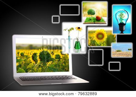 Laptop and eco theme images on dark grey background