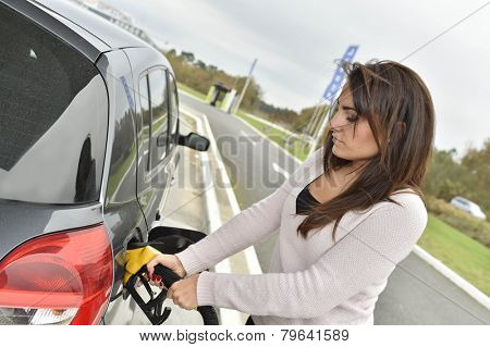 Young woman filling her car tank at gas station