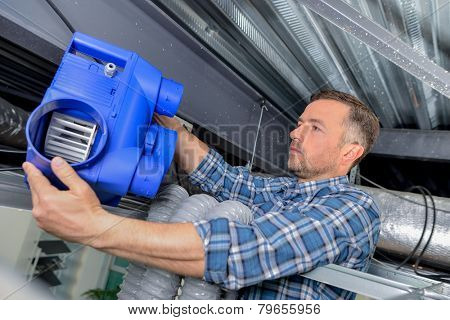 Electrician fitting a ventilation system