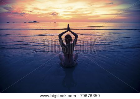 Yoga silhouette, exercises on the beach.