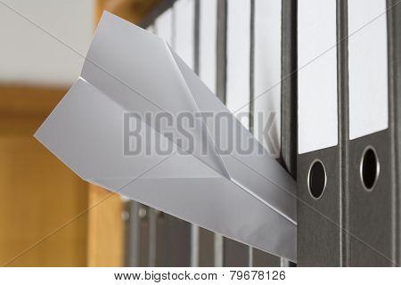 Paper Plane Stuck Between Folders