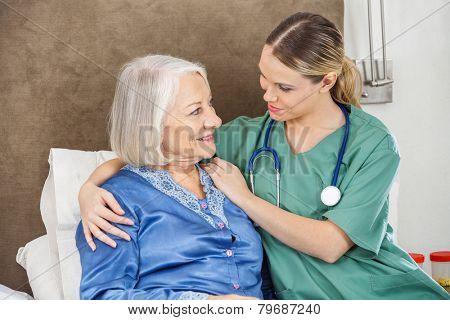 Female caretaker comforting senior woman in bedroom at nursing home