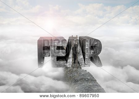 Businessman Climbing Ladder Conquering Fear Word On Ridge With Sunlight