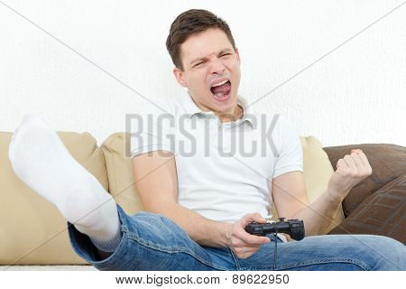 Guy At Home In Room Sitting On Bed With Thrilled Face Expression