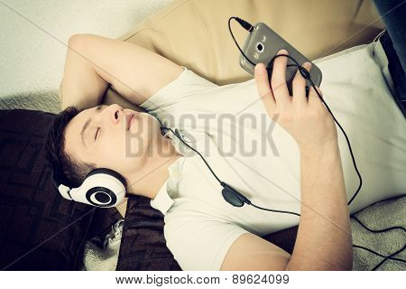 Man On Couch Holding Smartphone Listening To Music With Headset