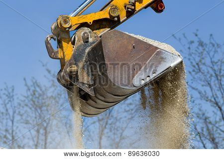 Close up of excavator bucket scooping gravel from pile for road construction poster