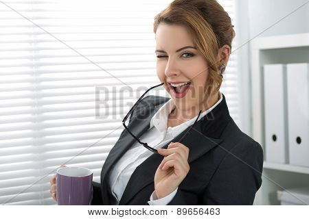 Playful Young Businesswoman Giving A Wink