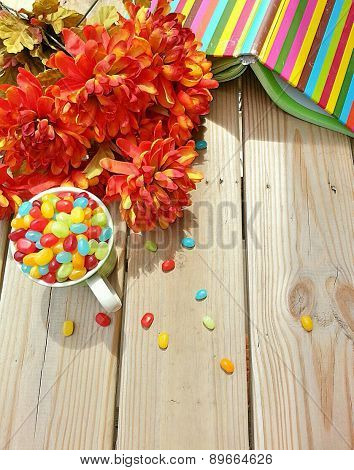 colorful book and jelly beans in a teacup and flowers