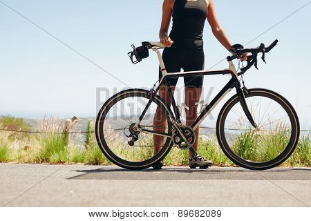 Female Athlete Standing With Her Bicycle