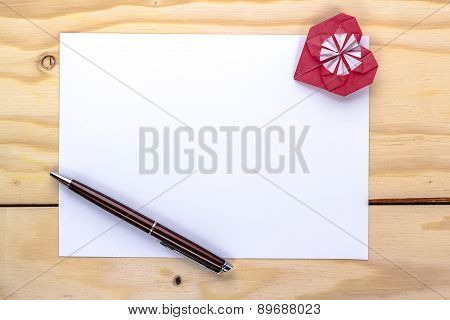 valentine letter with origami heart on wooden table