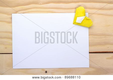 yellow origami heart and white paper sheet for love letter.