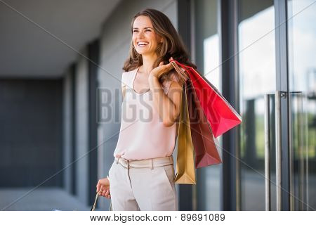 Smiling Woman With Three Shopping Bags Looking Into Distance