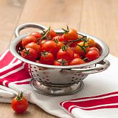 Freshly washed ripe tomatoes in colander on kitchen table poster