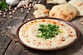 Hummus traditional Jewish creamy lunch salad with chickpeas, olive oil and paprika. Served with fresh backed pita bread poster