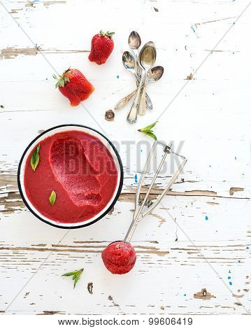 Strawberry sorbet or ice-cream with fresh berries, mint and metal scooper on over white rustic woode