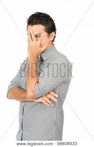 Profile of good looking latino man in casual clothes button-down dress shirt hand covering face eye peeking through split finger showing shy fearful emotions. Half vertical poster