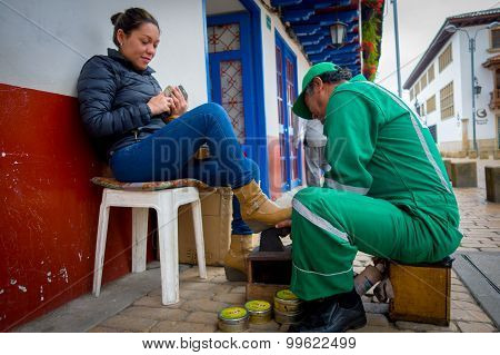 Unknown shoeshiner working in the center of historic Zipaquira city, located in the middle of Colomb