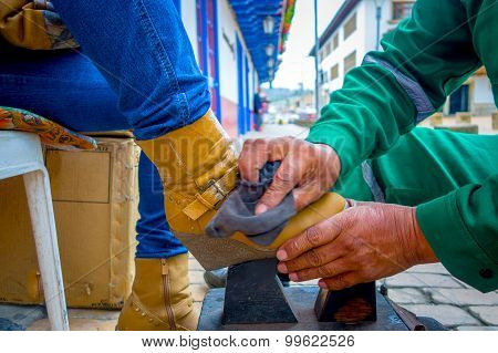Closeup of shoeshiner working on yellow boots in the center, historic Zipaquira city, located middle