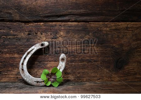 St. Patricks day, lucky charms. Four leaved clover and a horseshoe on wooden board poster