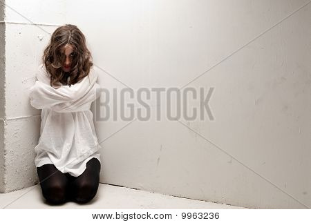 Young Insane Woman With Straitjacket On Knees Looking At Camera