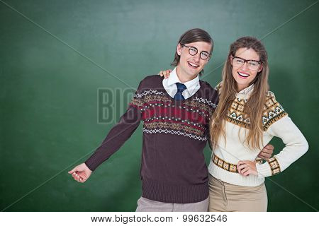 Happy geeky hipster couple embracing against green chalkboard