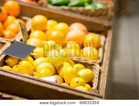 sale, shopping, vitamin c and healthy food concept - ripe lemons in basket with nameplate at grocery market