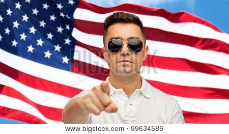 summer, accessories, style, gesture and people concept - face of middle aged latin man in white polo t-shirt and sunglasses pointing finger on you over american flag background