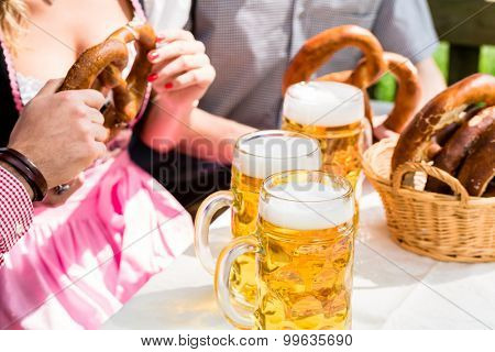 Glasses of beer and pretzel in German beer garden, close-up on the drinks and food
