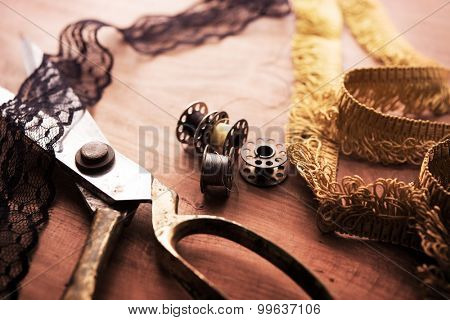 Fringe or lace tapes and silk trimmings with gold (brass) scissors and old sewing machine bobbins on a old grungy work table. Tailor's workbench. textile or fine cloth making.Shallow depth of field.