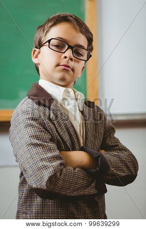 Portrait of pupil dressed up as teacher with arms crossed in a classroom