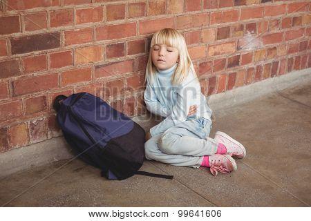 Sad pupil sitting alone on ground at corridor