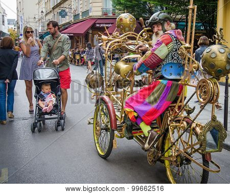 Man dressed in a fanciful Jules Verne costume rides his cycle in the streets of Marais
