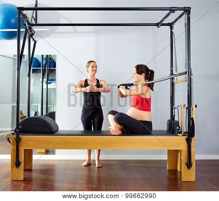 pregnant woman pilates reformer cadillac arms exercise workout with personal trainer poster