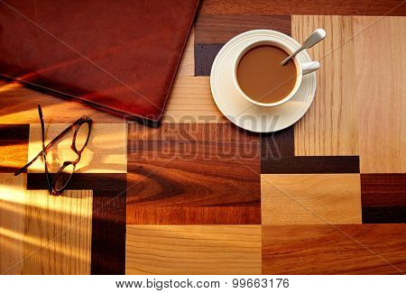 Coffee cup with glasses and leather folder on table retro vintage