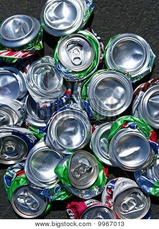 top view of a pile of crushed aluminum soda cans on asphalt