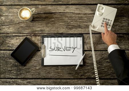 Overhead view of telephone operator making survey on the phone with a sheet of paper digital tablet phone and cup of coffee on his rustic wooden desk. Concept of telemarketing and customer feedback. poster