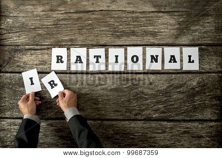 Overhead View Of Male Hands Taking Away Letters Ir From The Word Irrational Spelled On White Cards