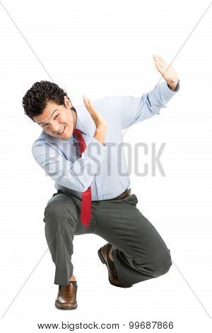 An intimidated latino man office worker in business attire crouching putting hands to shield in self defense protecting against verbal physical abuse assault off-screen. Workplace violence poster