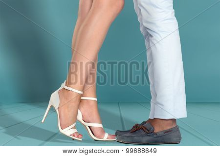 Legs Of Young Couple Against White Wall