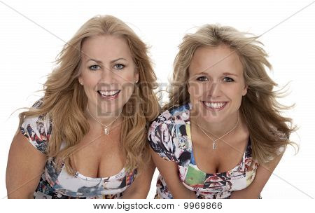 Studio photo of two attractive blonde women smiling at camera. Windblown hair white background. poster