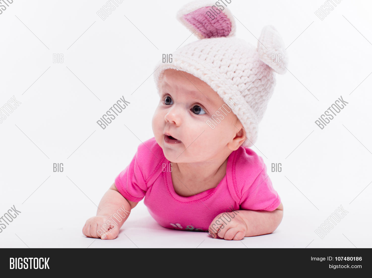 8eb21acbc0e5 cute baby girl lying in a bright red T-shirt on a white background wearing  a hat in the form of a Christmas bunny with pink ears and tail with depth  of ...