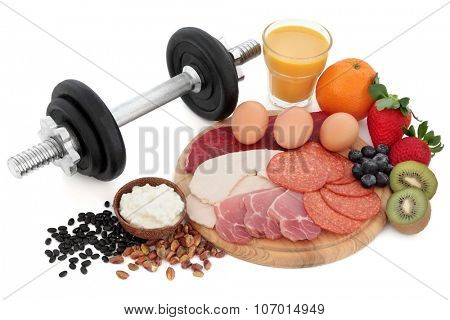 Health and body building high protein food of meat, nuts, pulses, cottage cheese, fruit and smoothie juice with dumbbell weights over white background.