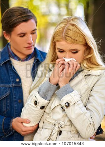 Woman with cold rhinitis on autumn outdoor. Fall flu season. Man looks with compassion on suffering of loved one.