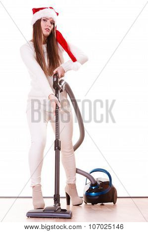 Woman vacuuming the house. Funny girl in santa helper hat with vacuum cleaner. Christmas time and housework concept. poster
